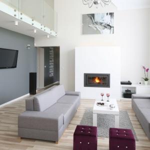 W otwartym na dwie kondygnacje salonie znalazło się wystarczająco dużo miejsca na elegancki kominek, jak i na ścianę z telewizorem. Tę ostatnią stylistycznie wyróżniono szarym kolorem, w którym są także kanapy. Projekt: Karolina i Artur Urban. Fot. Bartosz Jarosz.