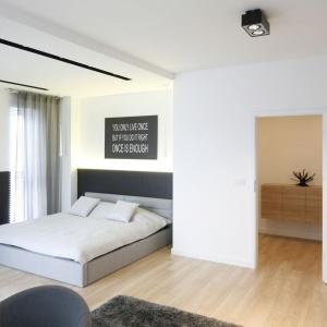 Posadzka na podłodze w sypialni i strefie dziennej jest taka sama, a płytki gresowe na ścianie przy łóżku dopasowano do obudowy kominka i wykończenia łazienki. Projekt: Karolina Stanek-Szadujko i Łukasz Szadujko. Fot. Bartosz Jarosz.