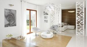 Elegancki dom został urządzony w bieli.To ona roztacza swą subtelną aurę przez lekkie formy mebli. Całość ociepla przytulny kolor drewna.