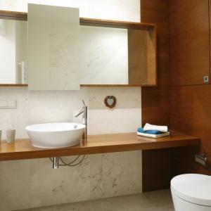 Drewno włazience ociepla jej wizerunek. Zastosowanie tego samego gatunku na ścianie imeblach sprawiło, że łazienka stała się bardzo przytulna. Projekt: Marta Kruk. Fot. Bartosz Jarosz.