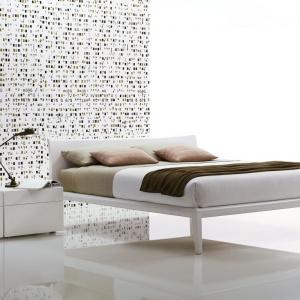 Minimalistyczne łóżko w bieli sprawdzi się w nowoczesnej sypialni. Ten model pasuje do dużych wnętrz, w których można go odpowiednio wyeksponować. Fot. Poliform.