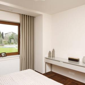 Duże okno w sypialni rozświetla przestrzeń i ożywia spokojną paletę kolorów, panującą w pomieszczeniu. Projekt: Piotr Stanisz. Fot. Bartosz Jarosz.
