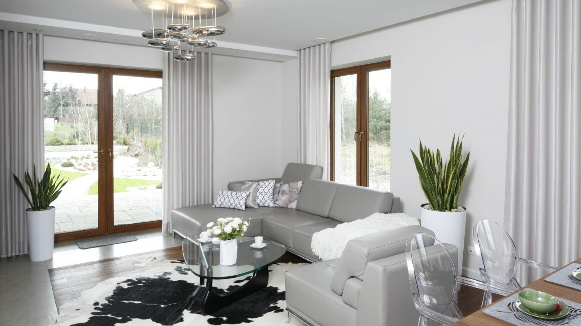 Domowa elegancja - tak można określić wystrój strefy wypoczynkowej. Kompozycję bieli i szarości uzupełniają stylowe dodatki i dekoracje. Całość tworzy nowoczesne, ale przytulne wnętrze. Projekt: Piotr Stanisz. Fot. Bartosz Jarosz.