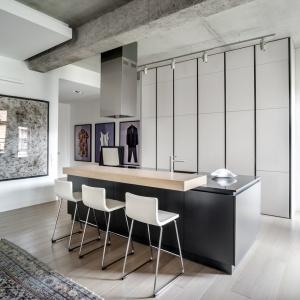 Minimalistyczna kuchnia, w której fronty wysokiej zabudowy wykończono białym lakierem a uchwyty i fronty wyspy kuchennej są w kolorze grafitowym. Elegancką kompozycję kontrastujących barw uzupełnia beton w aranżacji kuchni. Fot. Zajc Kuchnie, kuchnia Z1. Projekt wnętrza: TYMA PROJEKT \ www.tymaprojekt.pl.