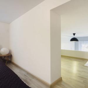Antresolę podzielono na dwie strefy. Pierwsza - otwarta na salon, to kącik czytelniczy i gabinet. W głębi natomiast urządzono wygodną sypialnię. Projekt: Patrycja Balińska-Seweryn i Mariusz Seweryn. Fot. właściciele.