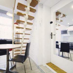 Na antresolę prowadzą segmentowe schody, które dzięki swojej konstrukcji nie przytłaczają przestrzeni. Miejsce pod schodami wykorzystano na wpasowanie małej jadalni. Duże lustro na ścianie powiększa optycznie przestrzeń. Projekt: Patrycja Balińska-Seweryn i Mariusz Seweryn. Fot. właściciele.