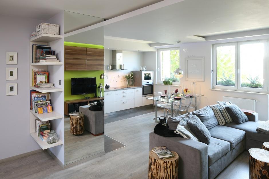 W otwartej strefie dziennej białą zabudowę kuchenną ulokowano na jednej ścianie, tworząc elegancki aneks kuchenny. Projekt: Arkadiusz Grzędzicki. Fot. Bartosz Jarosz.