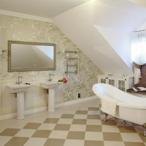 To bardzo elegancka łazienka. Wanna o pięknym kształcie, stylowa bateria oraz kwiecista tapeta nadają jej charakteru. Projekt: Maciej Bołtruczuk. Fot. Bartosz Jarosz.