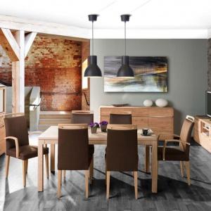 Połączenie nowoczesności i klasyki. Meble do jadalni są utrzymane w jasnym, dębowym kolorze drewna, mają proste, geometryczne formy. Efektownym zdobieniem jest metalowa wstęga spinająca poszczególne elementy kolekcji. Całość wieńczą krzesła z brązowym obiciem. Fot. Klose, jadalnia K19.