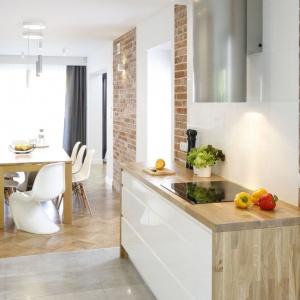 Oprócz połyskującej bieli, nad blatem w kuchni zastosowano również pasy starej, rozbiórkowej cegły. Projekt: Agata Piltz. Fot. Bartosz Jarosz.