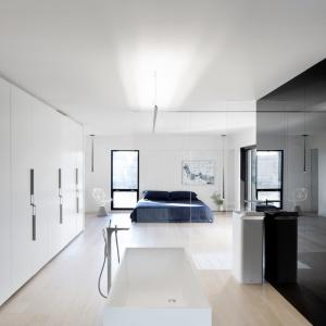 Łazienka zajmuje wspólną strefę z sypialnią. W jednej linii stoi duże małżeńskie łoże i nowoczesna, kubistyczna wanna. Strefę spania od salonu kąpielowego oddziela delikatne przeszklenie. Projekt: Marie-Pierre Auger Bellavance, Studio Practice. Fot. Adrien Williams & Gorgin S. Fazli.