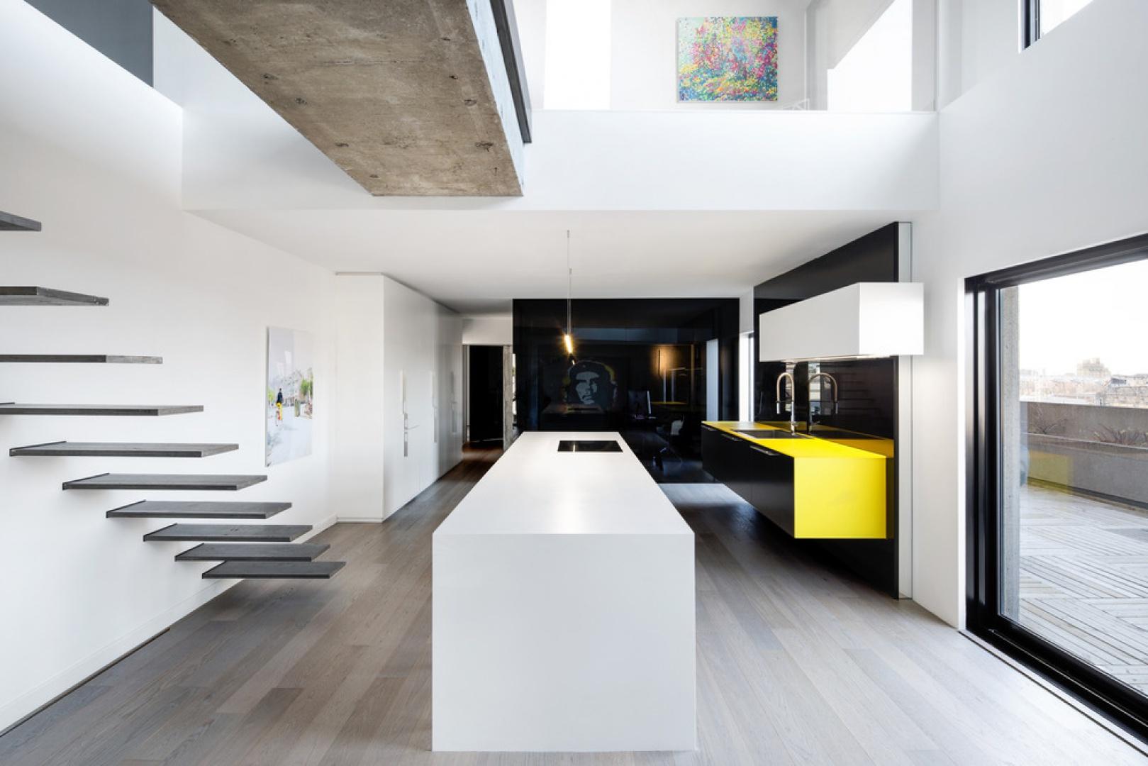 W aranżacji wnętrza dominują geometryczne formy. W kuchni ciąg komunikacyjny wyznacza duża wyspa o gładkich powierzchniach i prostych liniach, wykonana z Corianu w kolorze białym. Projekt: Marie-Pierre Auger Bellavance, Studio Practice. Fot. Adrien Williams & Gorgin S. Fazli.