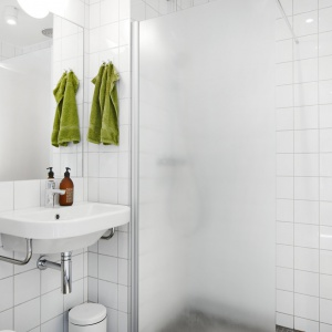 W łazience również króluje biel, ocieplone drewnianymi elementami. Fot. Vastanhem.