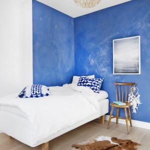 Jedną z sypialni urządzono w iście marynistycznym stylu. Ściana jest błękitna i stylizowana na postarzaną, a wieńczy ją morska fotografia. Fot. Vastanhem.