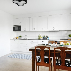 Drewniany stół kontrastuje z białą zabudową kuchenną. Elementem wypośrodkowanym jest drewniana podłoga w kolorze jasnego, bielonego drewna. Fot. Vastanhem.