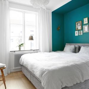 Sypialnia małżeńska pomieściła duże łoże, wpasowane we wnękę. Strefę spania dodatkowo zaznaczono innym kolorem - intensywnym turkusem. Fot. Vastanhem.