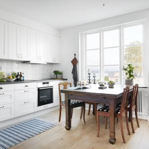 Oprócz indywidualnej jadalni, w mieszkaniu jest jeszcze druga - usytuowana w kuchni. Solidny stół z litego drewna pomieści do 6 osób. Fot. Vastanhem.