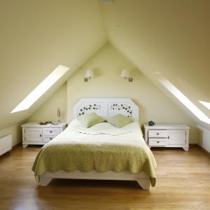 Sypialnia na poddaszu urządzona w kremowych beżach będzie przytulnym miejscem, pełnym ciepła. To doskonałe rozwiązanie do sypialni, w której wieczorami potrzebujemy się wyciszyć. Projekt: Agnieszka Kubasik. Fot. Bartosz Jarosz.
