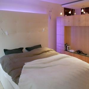 Duża sypialnia w domu jednorodzinnym. Pojemna meblościanka oraz podświetlona ściana za łóżkiem tworzą klimat tego wnętrza. Projekt: Zbigniew Tomaszczyk. Fot. Tomasz Augustyn.