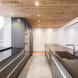 Część powierzchni roboczej sąsiaduje z przeszkleniem, wyglądającym na schody. Projekt: MU Architecture. Fot. Julien Perron-Gagné.