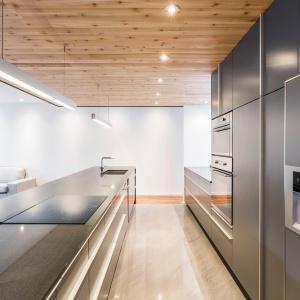 Szarości zamykają z dwóch stron drewniana podłoga i sufit. Ciepły odcień drewna dodaje kuchni przytulnego charakteru. Projekt: MU Architecture. Fot. Julien Perron-Gagné.