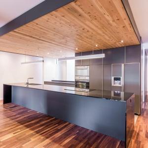 Kuchnia jest na wskroś nowoczesna. Wysoka zabudowa oraz długa wyspa, na której urządzono powierzchnię zmywania oraz gotowania. Razem z sufitem całość tworzy efektowny kubik. Projekt: MU Architecture. Fot. Julien Perron-Gagné.