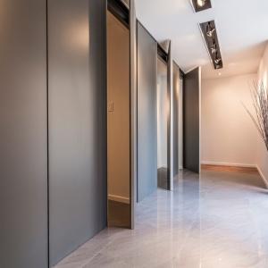 Mieszkanie urządzono w minimalistycznym stylu - pełno jest schowków, umożliwiających pochowanie w wysokiej zabudowie wszelkich sprzętów domowych i rupieci. Projekt: MU Architecture. Fot. Julien Perron-Gagné.