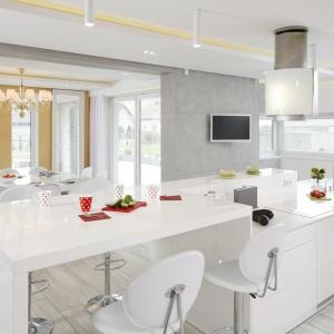 W tej nowoczesnej, minimalistycznej kuchni, długa wyspa zyskała przedłużenie w postaci wysokiego baru/stołu, przy którym domownicy mogą zjeść śniadanie lub mniejszy obiad. Projekt: Dominik Respondek. Fot. Bartosz Jarosz.