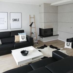 Jak przystała na stylistykę loft we wnętrzu nie mogło zabraknąć betonu. Zdobi on całą ścianę z kominkiem. Projekt: Beata Kruszyńska. Fot. Bartosz Jarosz.
