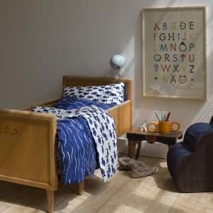 W małej sypialni przydaszą się meble mobilne, które można przesunąć. Stolik nocny na wysokich nóżkach nada wnętrzu lekkości. Na zdjęciu kolekcji Fish Wave Blue Duvet. Fot. Lo and Behold Store.