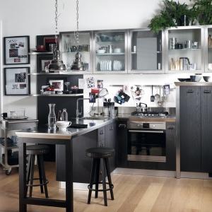 Industrialna kuchnia przywodzi na myśl laboratorium z początków XX wieku. Ciemnoszare fronty kuchenne, stalowe lampy nad półwyspem oraz vintage'owe stołki tworzą harmonijną całość. Fot. Scavolini/Diesel, Social Kitchen.