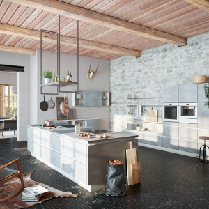 Szara cegła na ścianie w kuchni, szare meble kuchenne oraz wysoki sufity z widocznymi belkami stropowymi nadają tej kuchni delikatnie loftowy charakter. Fot. Wellmann.