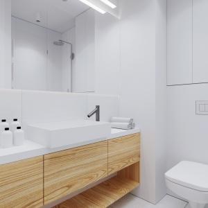 Łazienka to królestwo bieli, subtelnie przełamanej ciepłym kolorem drewna w postaci szafki umywalkowej. Projekt i wizualizacje: 081 Architekci.