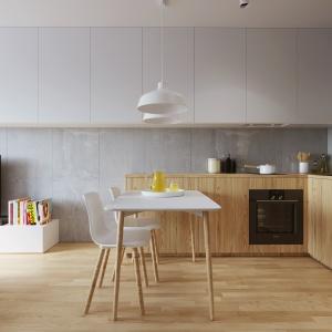 Ścianę nad blatem przesłonięto dyskretnym przezroczystym szkłem. Chroni ono powierzchnię przed zabrudzeniami, wynikłymi z użytkowania kuchni, a jednocześnie nie zaburza koncepcji aranżacyjnej całej strefy dziennej. Projekt i wizualizacje: 081 Architekci.