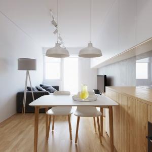 Umowną granicę pomiędzy kuchnią i salonem wyznacza niewielki stół jadalniany, nad którym zawisły dwie eleganckie, białe lampy. Projekt i wizualizacje: 081 Architekci.
