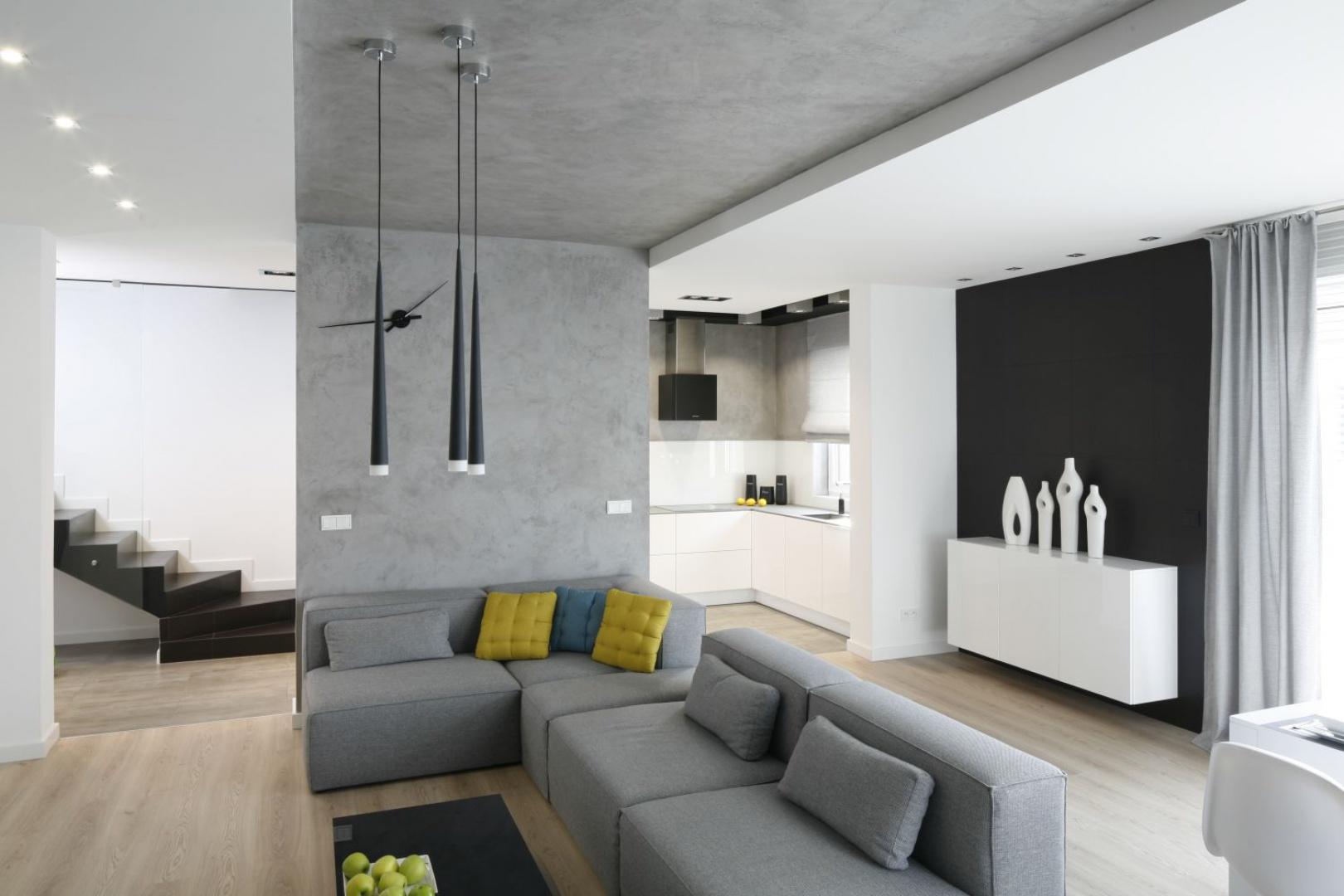 Wnętrze domu funkcjonuje jako chłodna baza, będąca tłem dla domowników. Architektom zależało na tym, aby stworzyć przestrzeń, w której człowiek będzie najcieplejszym dodatkiem, a wybór szarości podyktowany został kontrastem, jaki tworzy z odcieniem ludzkiej skóry. Projekt: Karolina Stanek-Szadujko, Łukasz Szadujko. Fot. Bartosz Jarosz.