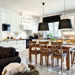 Delikatnie klasycyzująca kuchnia w skandynawskim stylu zyskała na przytulności dzięki frezowaniom na frontach zabudowy kuchennej, zasłonom w oknach oraz dużych, tekstylnych abażurach nad stołem jadalnianym. Projekt: Małgorzata Błaszczak. Fot. Pracownia Mebli Vigo.