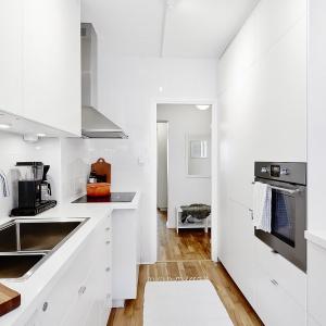 Biała zabudowa kuchenna jest utrzymana w prostej stylistyce z gładkimi frontami i wieńczącymi je metalowymi uchwytami. Fot. Vastanhem.se.