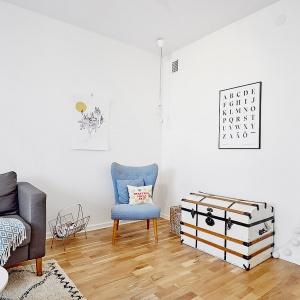 W rogu pomieszczenia urządzono kącik czytelniczy. Na wygodnym, eleganckim fotelu można usiąść w świetle edisonowskiej żarówki, zwisającej z odsłoniętego oplotu i poczytać czasopisma. Fot. Vastanhem.se.