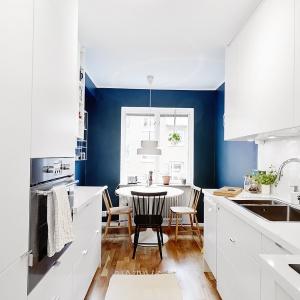 """Aby optycznie poszerzyć kuchnię i nieco ją """"skrócić"""" zastosowano ciemniejszą farbę na ścianach zamykających wnętrze od strony okna. Fot. Vastanhem.se."""