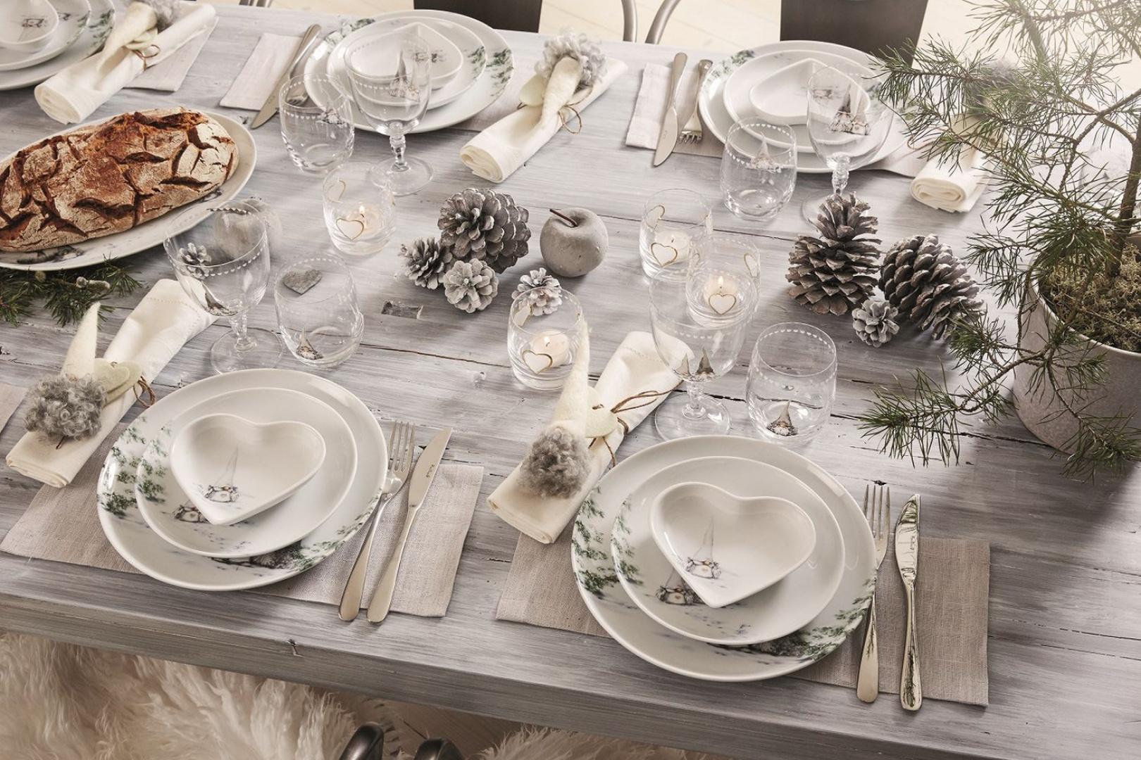 Wielbiciele skandynawskiej stylistyki z pewnością docenią aranżację, w której zamiast obrusu tło dla zastawy i dekoracji stanowi... sam drewniany stół. Z bielonym drewnem pięknie harmonizuje biało-zielona porcelana z kolekcji Asa's Christmas, kryształy i posrebrzane szyszki. Fot. Fyrklovern.