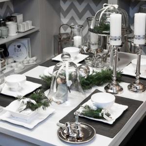 Elegancka biała porcelana i srebrne dodatki sprawiają, że stół prezentuje się bardzo stylowo. Chłodną elegancję przełamuje wesoły aniołek skrywający się pod szklanym kloszem. Fot. Decoratore.pl.