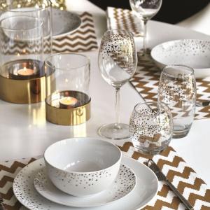 Elegancki efekt osiągniemy łącząc proste formy z bogatymi kolorami. Tutaj porcelana, szkło i świeczniki są utrzymane w minimalistycznym kształcie i ozdobione złotymi paskami, gwiazdkami i paskami. Fot. F&F Home.