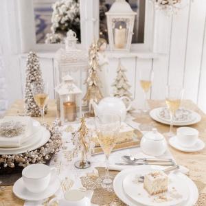 Śliczna aranżacja ze złotem i bielą w roli głównej. Na złotym obrusie położono biały bieżnik z motywem złotym choinek, a pod talerzami ułożono ażurowe, złote, tekstylne podkładki. Złote wzory zdobią również dekoracyjną latarenkę zastępującą świecznik i kieliszki. Całość tonuje prosta, biała porcelana. Fot. Home&You.