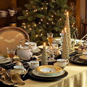 Stół na bogato. Piękna aranżacja zdominowana przez odświętny kolor złota. Złoty jest tutaj obrus, dekoracyjne chonki-świeczniki oraz ozdobne paski na białej porcelanie. Fot. Villa Italia.
