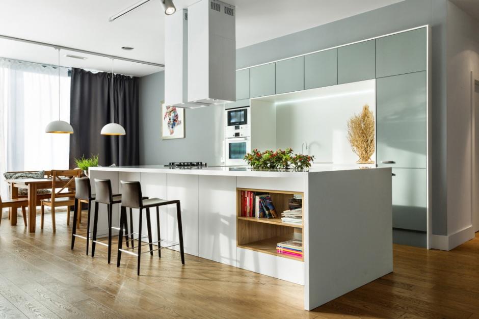 Podczas gdy dronty dużej wyspy, stanowiącej centrum kuchni, wykończono w białym macie, wysoką zabudowę wieńczą fronty w miętowym kolorze i wysokim połysku. Fot. Pracownia Mebli Vigo, kuchnia Nuvola.
