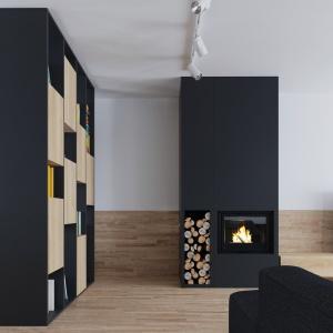 W mieszkaniu panuje kolorystyczna harmonia. Połączenie grafitowej czerni z jasnym wybarwieniem drewna odzwierciedla również zabudowa kominka i poukładane w niej drewno na opał. Projekt i wizualizacje: 081 Architekci.