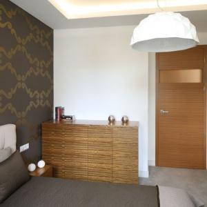 Ścianę w sypialni udekorowano grafitowo-złotą tapetą. Wprowadza ona do wnętrza odrobinę stylistyki glamour. Projekt: Małgorzata Galewska. Fot. Bartosz Jarosz.