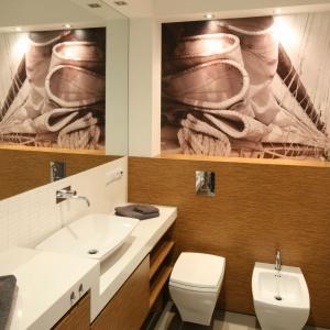 W łazience nad stelażem wc, a także w strefie prysznica ściany udekorowano fototapetą z marynarskim motywem. Fotografie są utrzymane w kolorze sepii, tak aby harmonizowały z panującą w mieszkaniu paletą barw. Projekt: Małgorzata Galewska. Fot. Bartosz Jarosz.