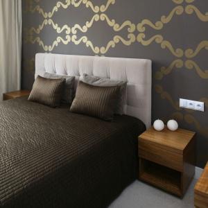 Tapicerowany zagłówek za łóżkiem wyeksponowany został poprzez kontrast ciemnej tapety z jasną kolorystyką obicia. Projekt: Małgorzata Galewska. Fot. Bartosz Jarosz.
